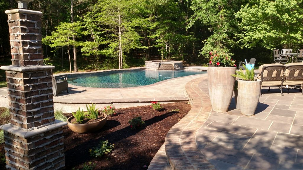 travertine deck with brick coping and landscaping